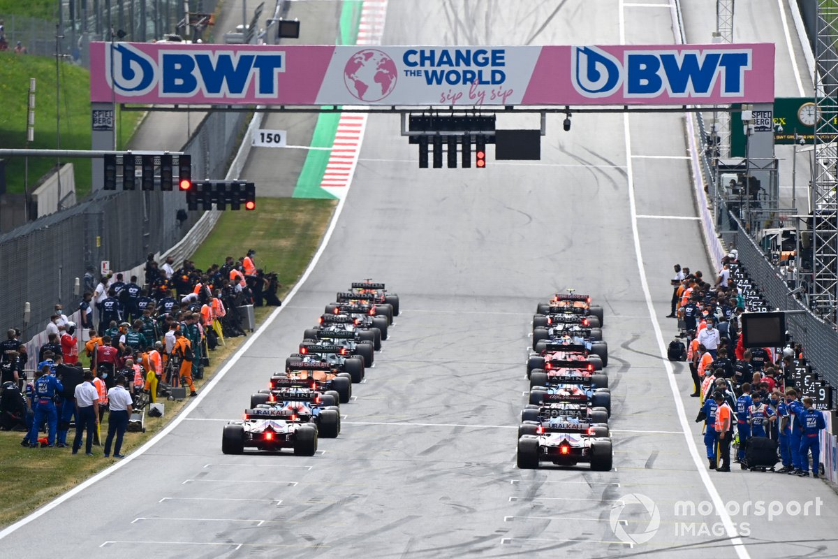 Max Verstappen, Red Bull Racing RB16B, and Lando Norris, McLaren MCL35M, prepare to lead the field away at the start